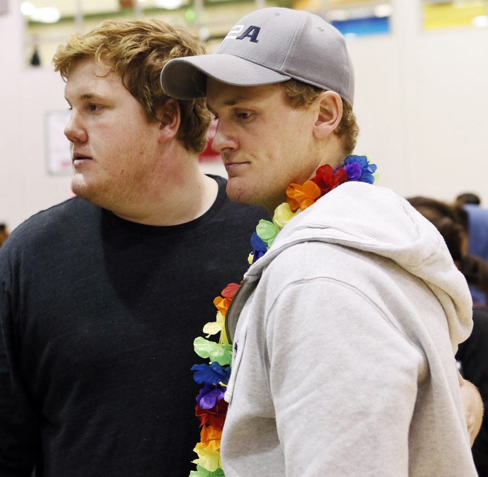 Photo - J.R. Hensley, left, puts his arm around older brother Ty Hensley after J.R. signed to play football at the University of Hawaii during a national signing day ceremony at Edmond Santa Fe High School in Edmond, Okla., Wednesday, Feb. 4, 2015. Ty Hensley also went to Edmond Santa Fe and is a Yankees prospect. Photo by Nate Billings, The Oklahoman