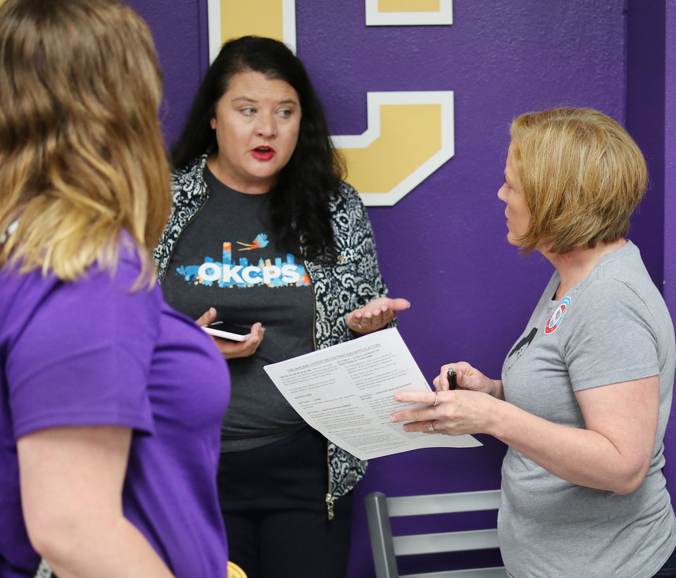 Photo - Amy Curran, center, answers a question from April Mays, right. Generation Citizen set up at Northwest Classen High School during lunch to register students age 17 and older to vote, Wednesday, September 25, 2019. [Doug Hoke/The Oklahoman]