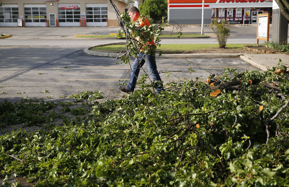 Photo - The Rev. Tobin Jackson clears trees from the parking lot of Trinity Baptist Church after an apparent tornado moved through the area in Oklahoma City, Sunday, May 26, 2019.  [Sarah Phipps/The Oklahoman]