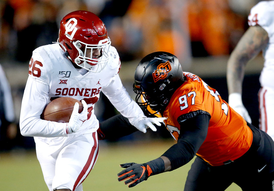 Photo - Oklahoma's Kennedy Brooks (26) looks to get by Oklahoma State's Amadou Fofana (97) in the fourth quarter during the Bedlam college football game between the Oklahoma State Cowboys (OSU) and Oklahoma Sooners (OU) at Boone Pickens Stadium in Stillwater, Okla., Saturday, Nov. 30, 2019. OU won  34-16. [Sarah Phipps/The Oklahoman]