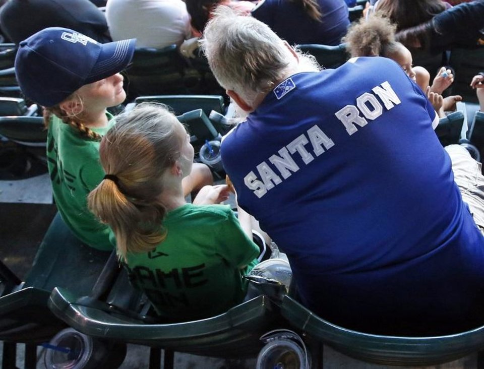 Photo - Ron Herendeen, known as Santa Ron, talks with Coley Richmond, 8, left, and Tenley Richmond, 8, as he and his Team Santa kids attend an Oklahoma City Dodgers baseball game at the Chickasaw Bricktown Ballpark in Oklahoma City, Friday, Aug. 24, 2018. Team Santa is a program to promote health and fitness in youngsters that Santa Ron started after he was diagnosed with Type 2 diabetes. Photo by Nate Billings, The Oklahoman