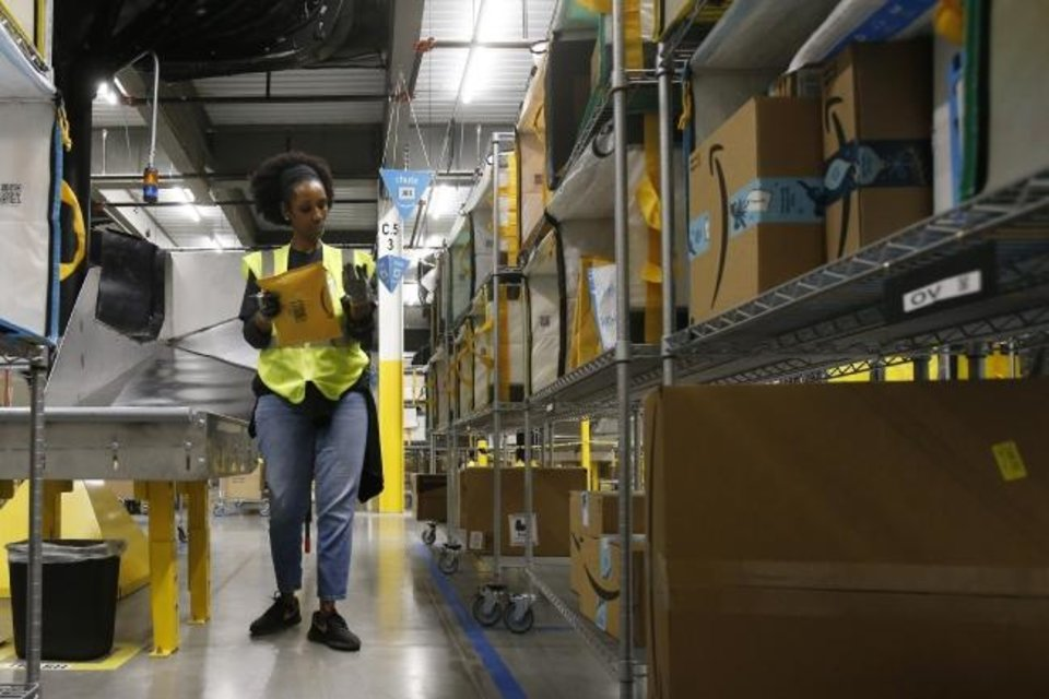 Photo -  Tahsha Sydnor stows packages into special containers in December at an Amazon warehouse facility in Goodyear, Ariz. [AP File Photo]