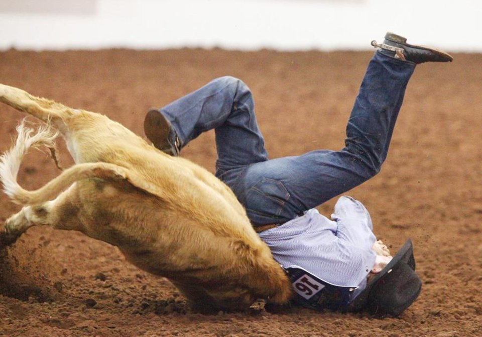 Photo -  Jim Ross Cooper rolls over his steer while competing in Steer Wrestling during the Timed Event Championships at the Lazy E Arena, Friday, March 4, 2011. Photo by David McDaniel, The Oklahoman  ORG XMIT: KOD