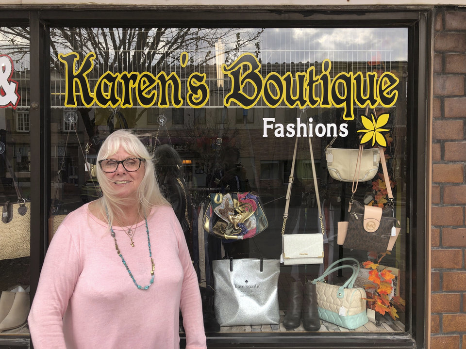Photo -  Karen Prohaska, 76, stands outside her purse and jewelry shop in downtown Plattsmouth, Nebraska, on Monday, Nov. 9, 2020. Prohaska says she hopes not to get the virus, but she usually doesn't wear a mask in her store because it hinders her breathing. She believes some people are overreacting to the threat. (AP Photo/Grant Schulte)