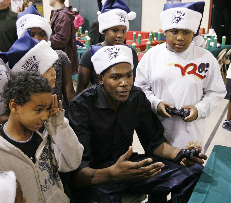 Photo - NBA basketball player Kevin Durant of the Oklahoma City Thunder reacts while playing video games during a holiday party for children in the after school program at Pilot Recreation Center, 1435 NW 2nd Street, in Oklahoma City, Wednesday, Dec. 17, 2008. At the end of the party, Kevin Durant gave the children winter coats, hats and gloves donated by Nike. BY NATE BILLINGS
