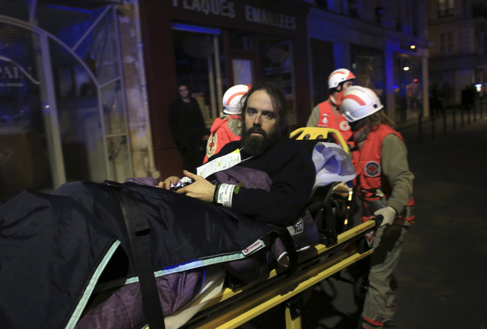 Photo - A man is being evacuated from the Bataclan theater after a shooting in Paris, Friday Nov. 13, 2015.  French President Francois Hollande declared a state of emergency and announced that he was closing the country's borders. (AP Photo/Thibault Camus)