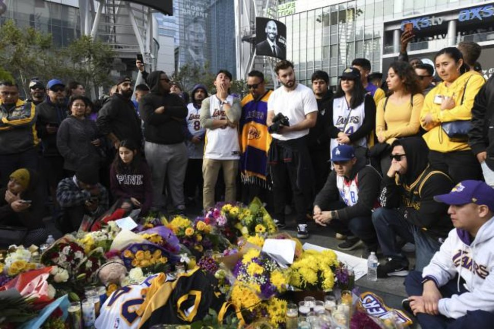 Photo -  People gather at a memorial for Kobe Bryant near Staples Center Sunday in Los Angeles. Bryant, the 18-time NBA All-Star who won five championships and became one of the greatest basketball players of his generation during a 20-year career with the Los Angeles Lakers, died in a helicopter crash Sunday. [AP Photo/Michael Owen Baker]