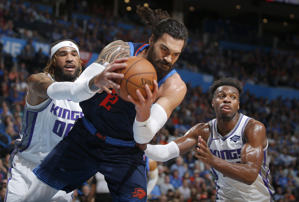 Photo - Oklahoma City's Steven Adams (12) reaches for the ball in front of Sacramento's Willie Cauley-Stein (00) and Buddy Hield (24) during an NBA basketball game between the Oklahoma City Thunder and the Sacramento Kings at Chesapeake Energy Arena in Oklahoma City, Sunday, Oct. 21, 2018. Photo by Bryan Terry, The Oklahoman
