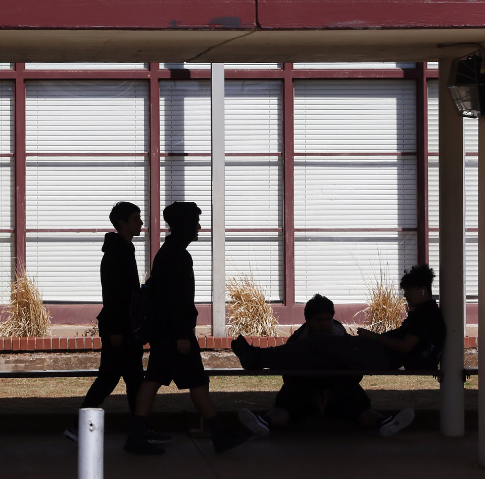 Photo - Students are silhouetted after school outside of Northwest Classen High School n Oklahoma City, Thursday, March 12, 2020. Oklahoma City Pubic Schools will be closed Friday, March 13, due to the new coronavirus before starting spring break the following week. [Nate Billings/The Oklahoman]