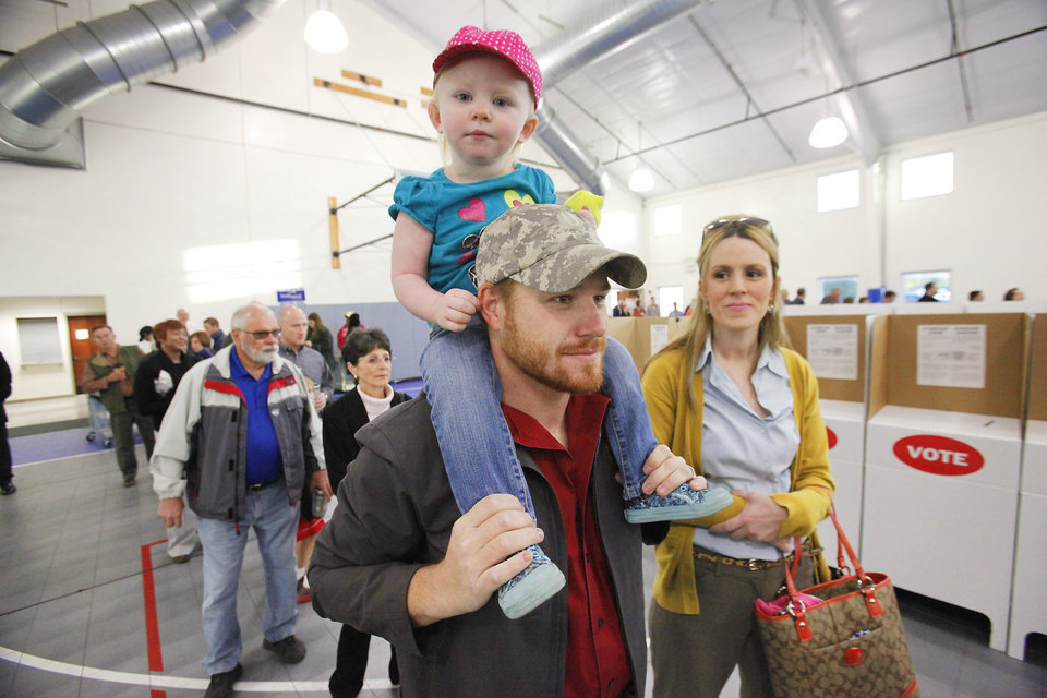 Photo - Ava Ward, 2, gets a birds eye view of the voters from her dad Brian's shoulders at precincts 40 at Holy Trinity Lutheran Church in Edmond, Tuesday, November 6, 2012.  Mom Emily is with them.  Photo By David McDaniel/The Oklahoman