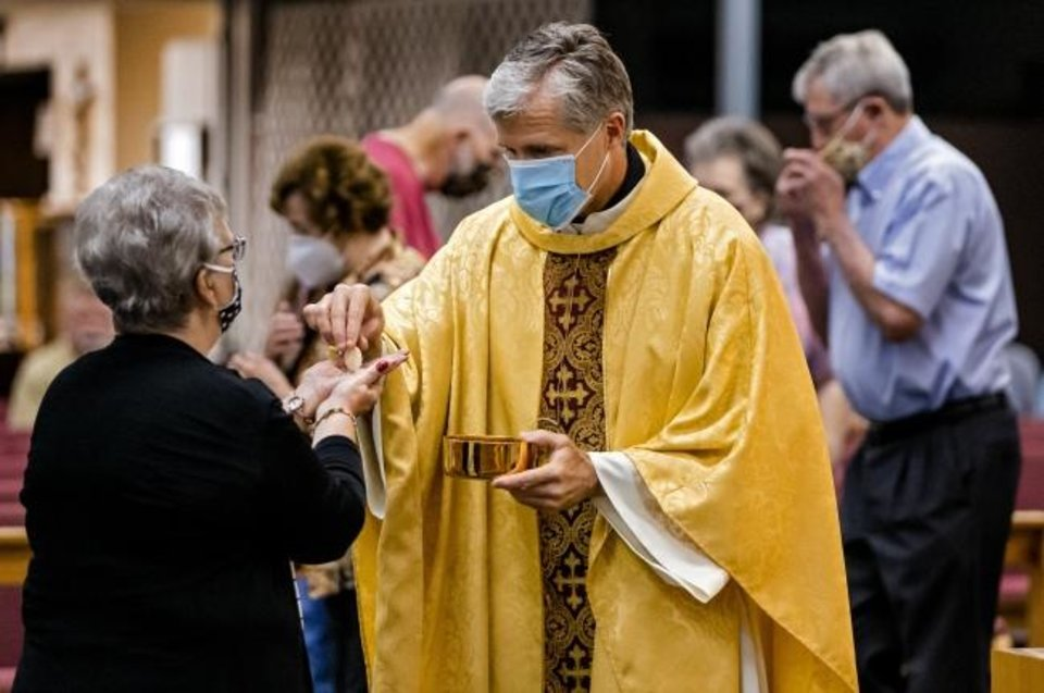 Photo -  A parishioner receives the Eucharist from the Rev. Joseph Jacobi during Mass at Holy Spirit Catholic Church in Mustang. [Chris Landsberger/The Oklahoman]
