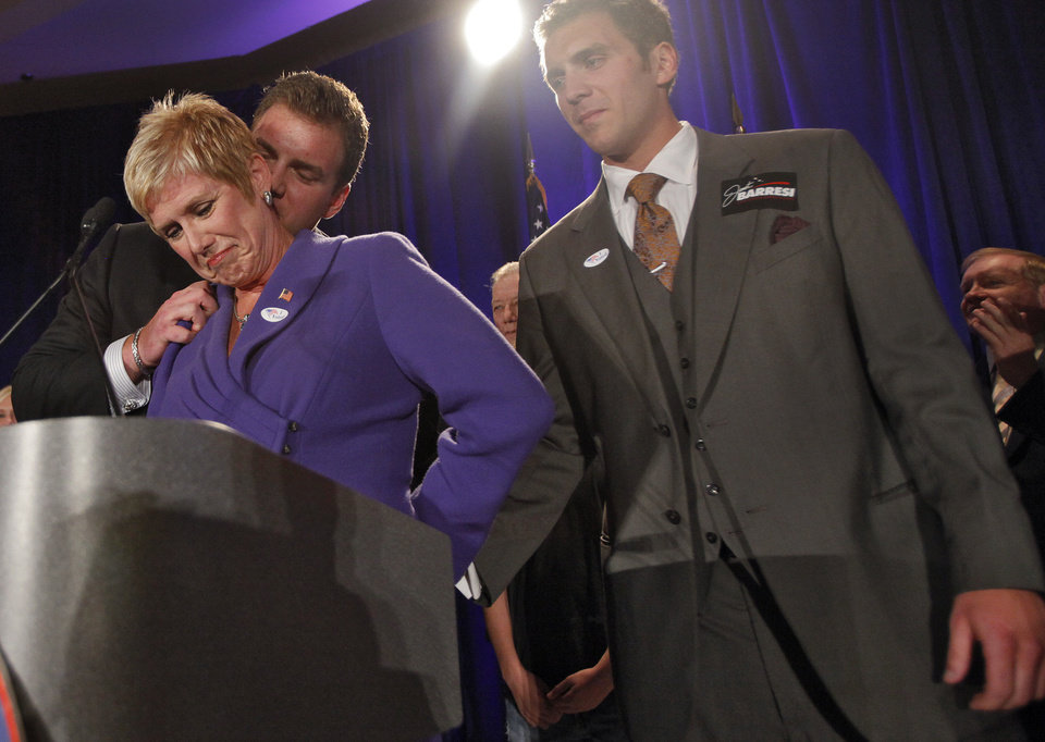 Photo - Janet Barresi is kissed on the neck by her son Joe as her other son Ben holds her hand during her speech at the republican Watch Party at the Marriott on Tuesday, Nov. 2, 2010, in Oklahoma City, Okla.   Photo by Chris Landsberger, The Oklahoman