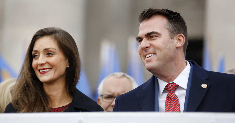 Photo - Gov. Kevin Stitt and his wife, Sarah, smile when they see familiar faces in the crowd from their seats on the platform at the inauguration ceremony where he was sworn in as Oklahoma's 28th governor by Supreme Court Chief Justice Noma Gurich on Monday, Jan. 14, 2019.  Photo by Jim Beckel, The Oklahoman.