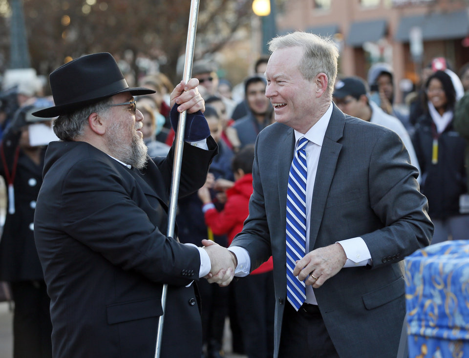 Photo - Rabbi Ovadia Goldman, left, shakes hands with Mick Cornett, mayor of Oklahoma City, after Cornett lit one of the lights on the Britcktown menorah during the annual Hanukkah menorah lighting event hosted by Chabad Jewish Center of Oklahoma City on the third base plaza outside of the Chickasaw Bricktown Ballpark, Monday, Dec. 26, 2016. Photo by Nate Billings, The Oklahoman