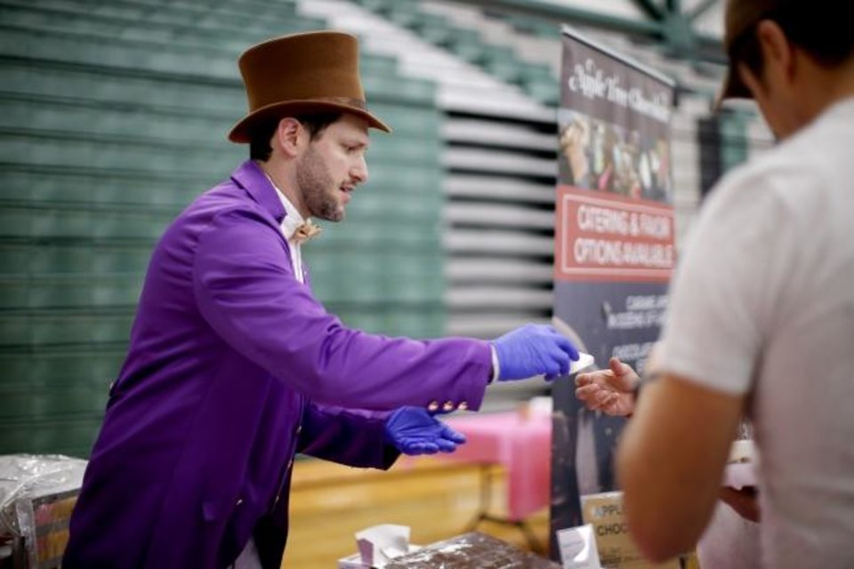 Photo -  Dressed as Willy Wonka, Scotty Jackson from Apple Tree Chocolate hands out chocolate-covered apples during Saturday's 38th annual Norman Chocolate Festival at Norman North High School.  [Bryan Terry/The Oklahoman]