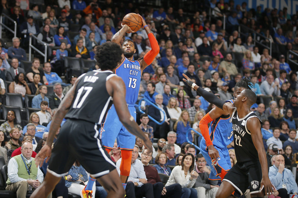 Photo - Oklahoma City's Paul George (13) shoots as  Brooklyn's Ed Davis (17)  and Caris LeVert (22) defend during an NBA basketball game between the Oklahoma City Thunder and the Brooklyn Nets at Chesapeake Energy Arena in Oklahoma City, Wednesday, March 13, 2019. Oklahoma City won 108-96. Photo by Bryan Terry, The Oklahoman
