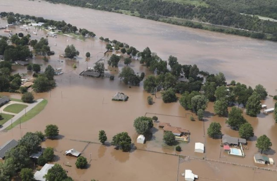 Photo -  In this aerial image, homes are inundated with floodwaters from the Arkansas River near South 145th West Ave near State Highway 51 on Thursday in Sand Springs.  [Tom Gilbert/Tulsa World]