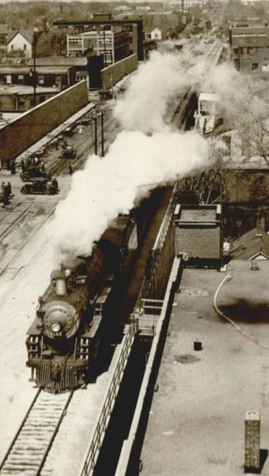 Photo -  A train heads north across elevated tracks downtown as a car passes underneath. [OKLAHOMA HISTORICAL SOCIETY]