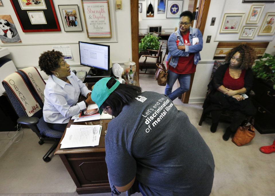 "Photo - Reynelda Tallent, Tulsa, signs the guest list when visiting the Capitol office of Sen. Kevin Matthews. She wears a shirt with the wording, ""Let's end the discrimination of mental illness.""   Tallent is with the Community Service Council in Tulsa where she works with a group, BRRX 4 Vets, assisting homeless veterans. Advocates for mental health care descended upon the state Capitol Tuesday morning, Oct. 24, 2017, to demand that lawmakers come up with a budget solution that includes funding for mental health services. Photo by Jim Beckel, The Oklahoman"