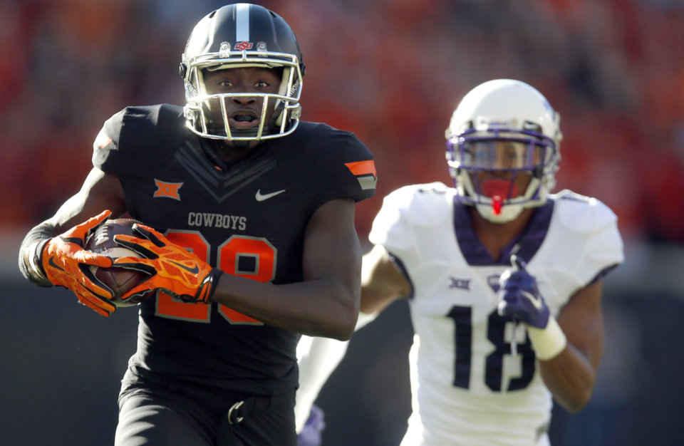 Photo - Oklahoma State's James Washington (28)) makes runs for a touchdown after a reception as TCU's Nick Orr (18) chases him in the first quarter during the college football game between the Oklahoma State Cowboys (OSU) and TCU Horned Frogs at Boone Pickens Stadium in Stillwater, Okla., Saturday, Nov. 7, 2015. Photo by Sarah Phipps, The Oklahoman