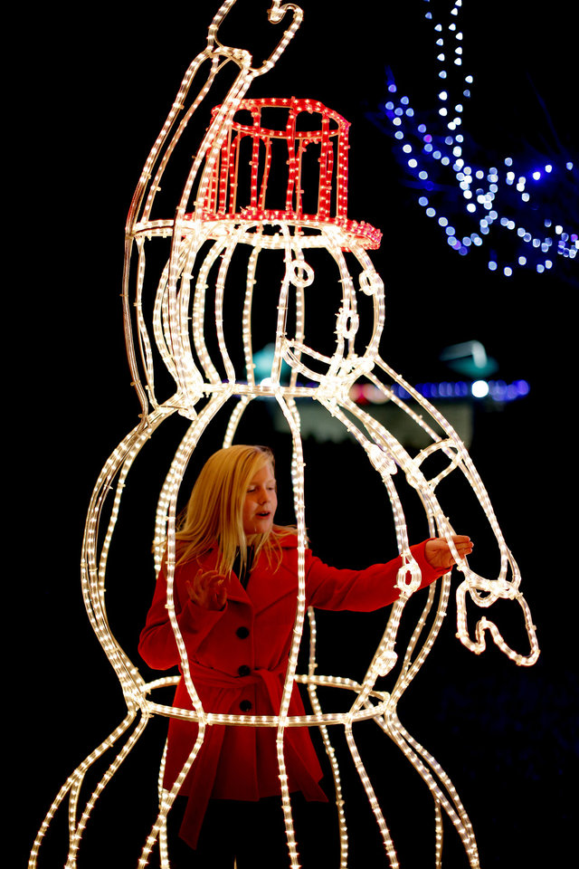 Photo - CHILD / CHILDREN / KIDS / HOLIDAY / CHRISTMAS LIGHTS: Annie Davis, 9, stands inside a lighted snowman during the Mayor's Tree Lighting at Shannon Miller Park in Edmond, Okla., Saturday, Dec. 8, 2012. Photo by Bryan Terry, The Oklahoman