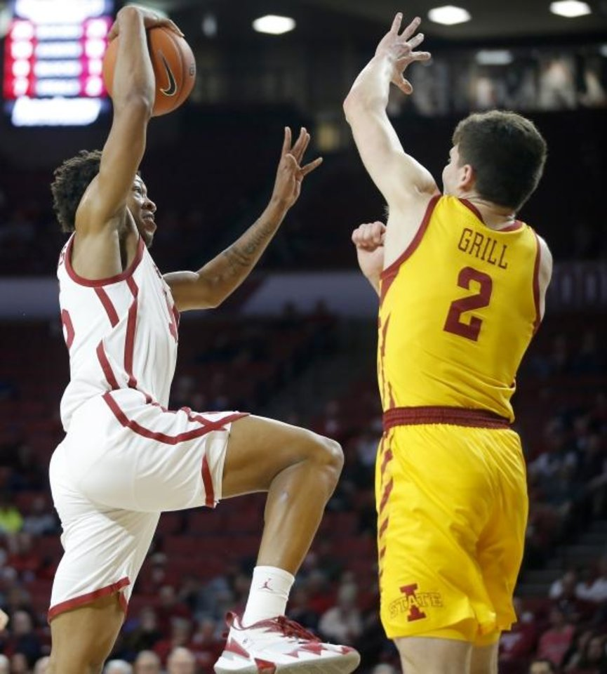 Photo -  Oklahoma's Alondes Williams, left, goes up to dunk beside Iowa State's Caleb Grill during Wednesday's game at Lloyd Noble Center in Norman. [Bryan Terry/The Oklahoman]