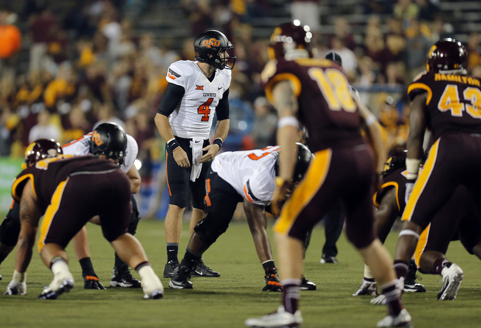 Photo - Oklahoma State's J.W. Walsh (4) lines up in the fourth quarter during the college football game between the Central Michigan Chippewas and the Oklahoma State University Cowboys at the Kelly/Shorts Stadium in Mount Pleasant, Mich., Thursday, Sept. 3, 2015. Photo by Sarah Phipps, The Oklahoman