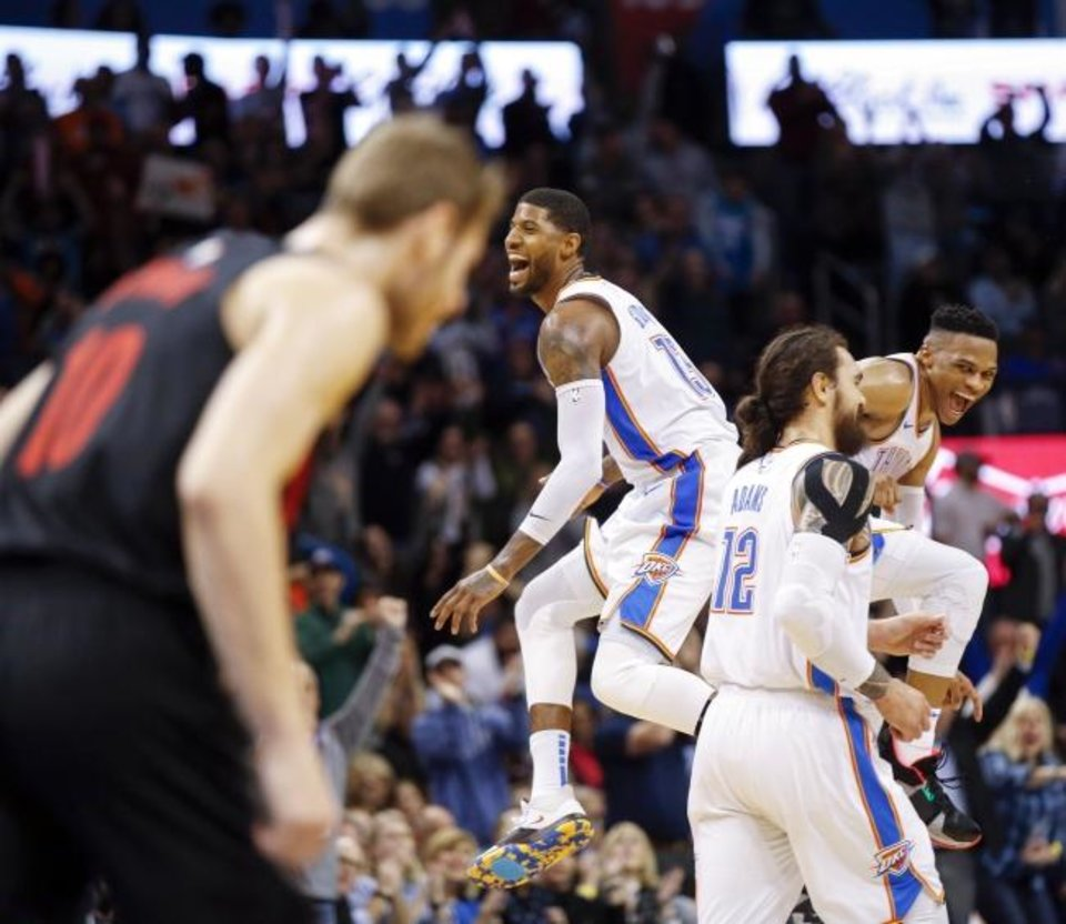 Photo -  Oklahoma City's Russell Westbrook), right, and Paul George celebrate near Steven Adams (12) after Westbrook made a basket on an assist from George in the final minute of the fourth quarter during a February victory over the Portland Trail Blazers. [Nate Billings/The Oklahoman]