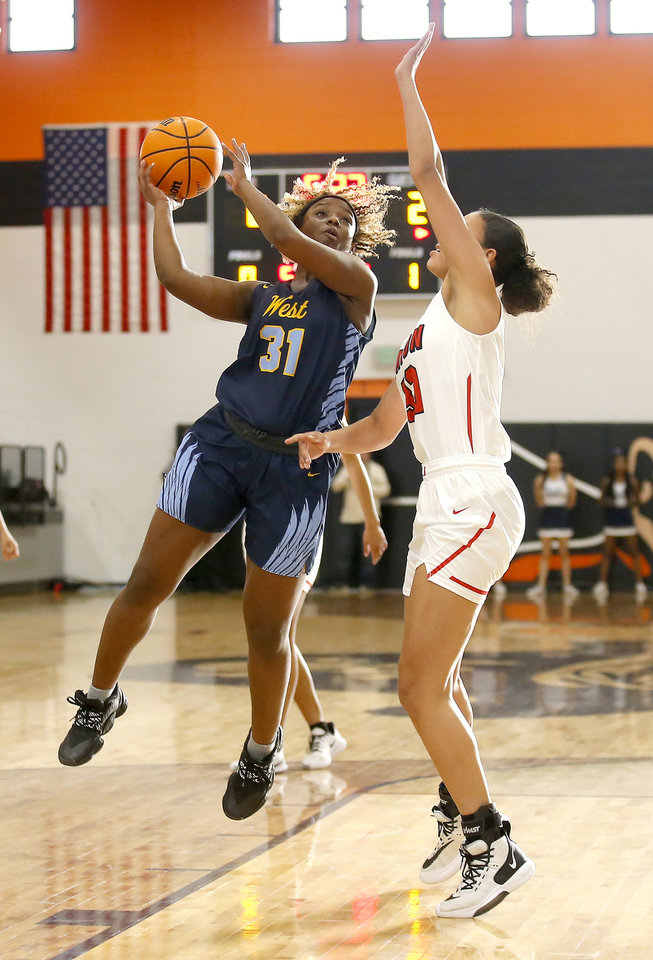 Photo - Putnam City West's Akile Stone goes to the basket as Union's Jayla Burgess defends during the girls championship game between Putnam City West and Tulsa Union at the Putnam City Invitational at Putnam City High School in Oklahoma City, Okla.,  Saturday, Jan. 11, 2020.  [Sarah Phipps/The Oklahoman]