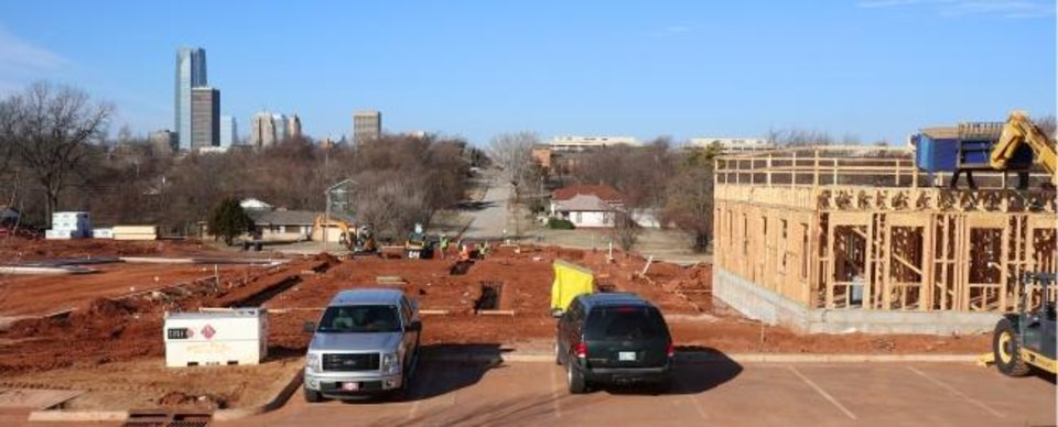 Photo -  The downtown skyline and the Oklahoma Health Center can be seen in the background as construction continues on the latest phase of housing being built by developer Ron Bradshaw as part of the transformation of the former Page Woodson school campus.  [Doug Hoke/The Oklahoman]