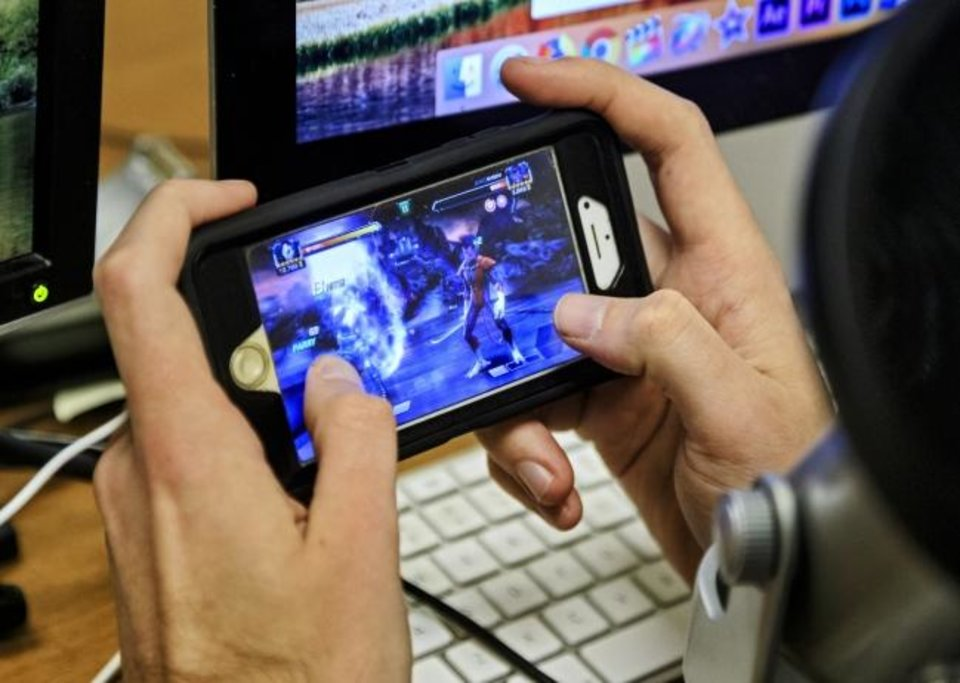 Photo -  Multimedia Journalism Professor Shane Hoffman plays the video game