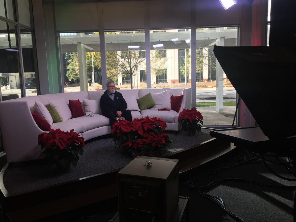 Photo - Rodney Bivens, executive director of the Regional Food Bank, in studio Monday. Trochta's Flowers and Garden Center has provided our set with some fantastic poinsettias.