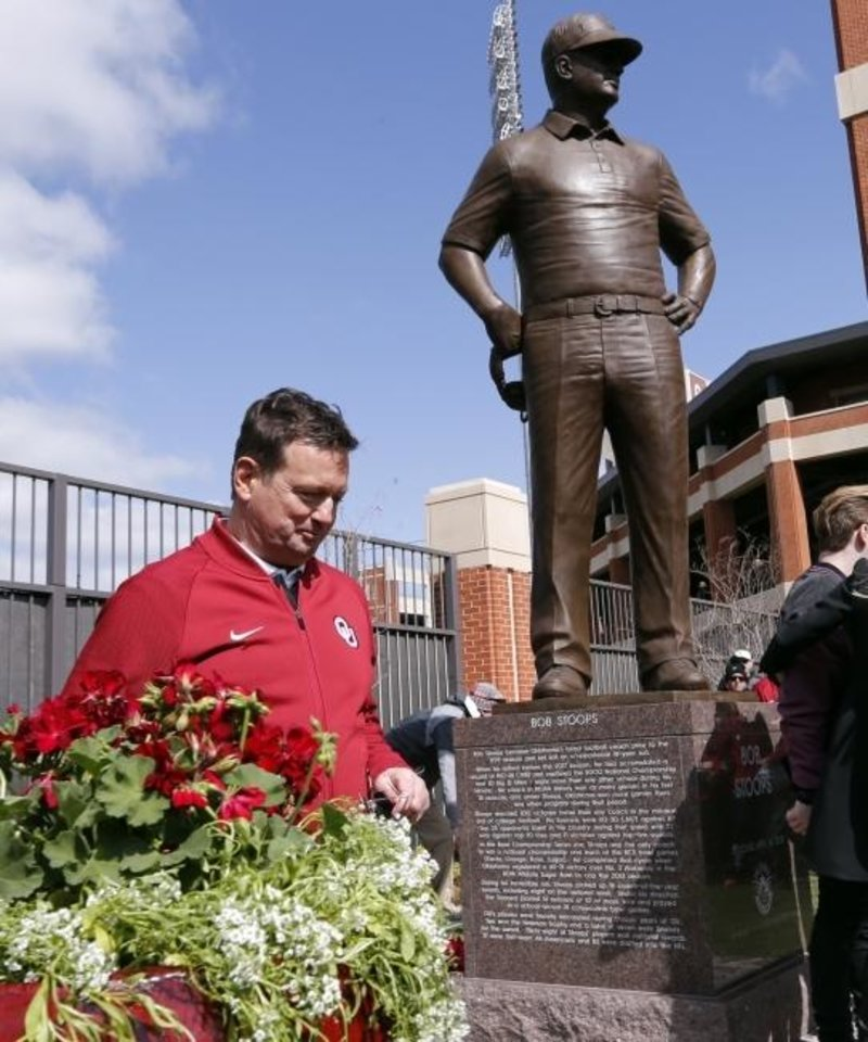 Photo -  Bob Stoops walks away from the statue erected in his honor. [Oklahoman archives]