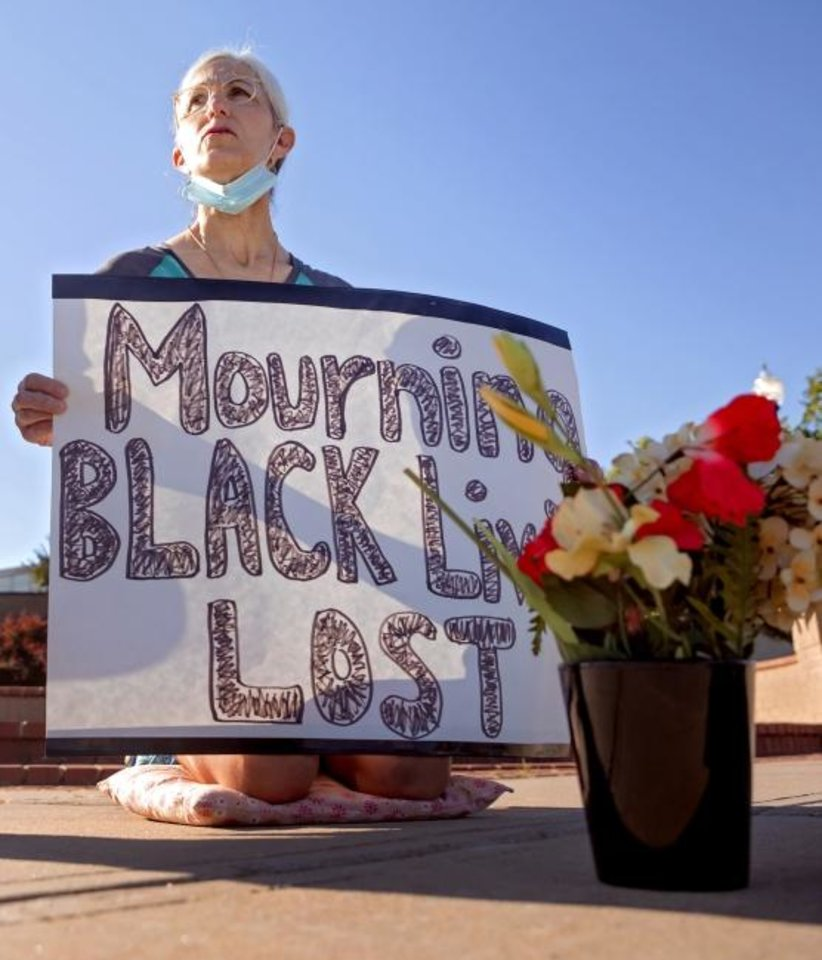 Photo -  Terry Fife of Forest Park kneels with her sign on the corner of NE 23 and Martin Luther King Avenue as morning traffic passes through the intersection. [Chris Landsberger/The Oklahoman]