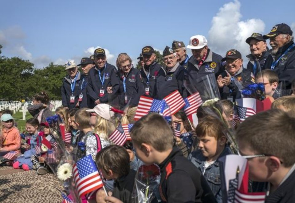 Photo -  World War II veterans from the United States pose with local schoolchildren at the Normandy American Cemetery in Colleville-sur-Mer, Normandy, France, on Monday. [AP Photo/Rafael Yaghobzadeh]