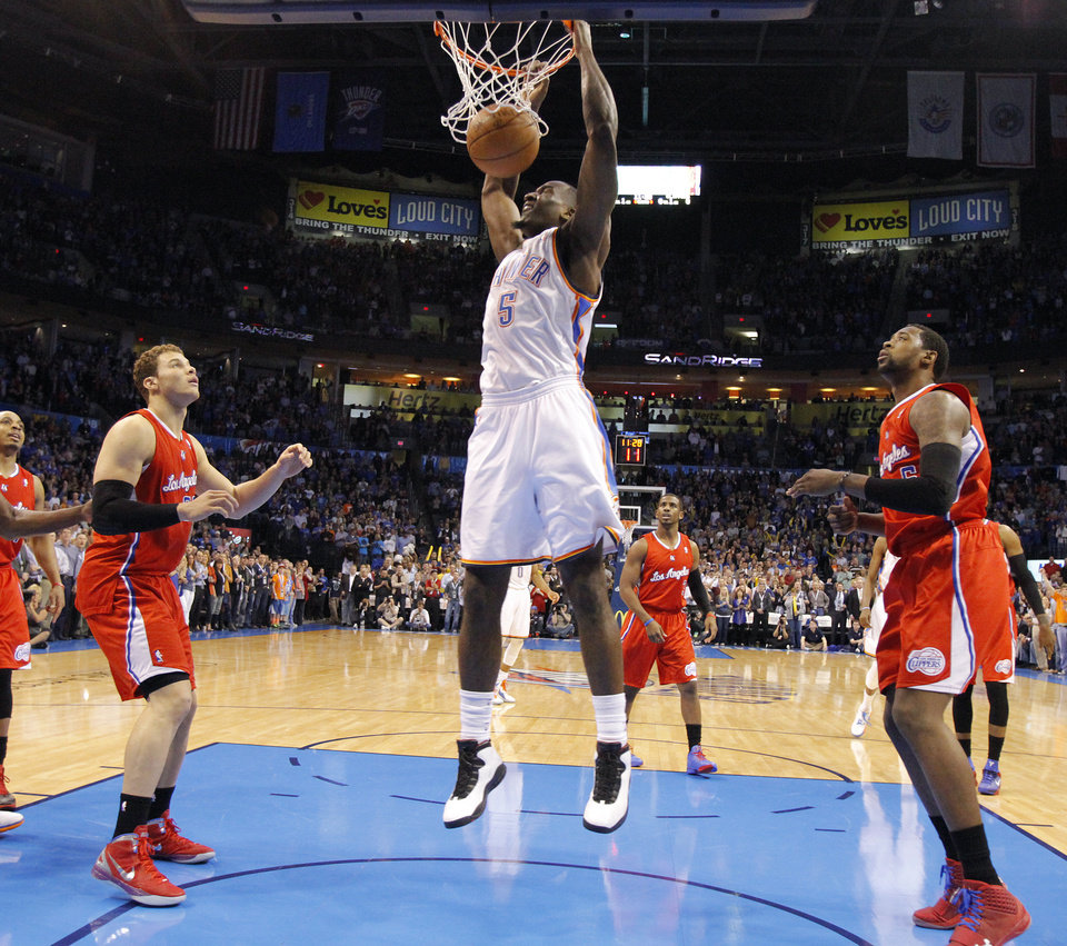 Photo - Oklahoma City Thunder center Kendrick Perkins (5) dunks the ball in front of Los Angeles Clippers power forward Blake Griffin (32) and Los Angeles Clippers center DeAndre Jordan (6) during the NBA basketball game between the Oklahoma City Thunder and the Los Angeles Clippers at Chesapeake Energy Arena on Wednesday, March 21, 2012 in Oklahoma City, Okla.  Photo by Chris Landsberger, The Oklahoman