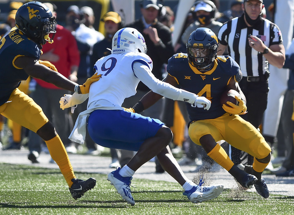 Photo - West Virginia running back Leddie Brown (4) rushes the ball against Kansas during an NCAA college football game, Saturday, Oct. 17, 2020, in Morgantown, W.Va. (William Wotring/The Dominion-Post via AP)