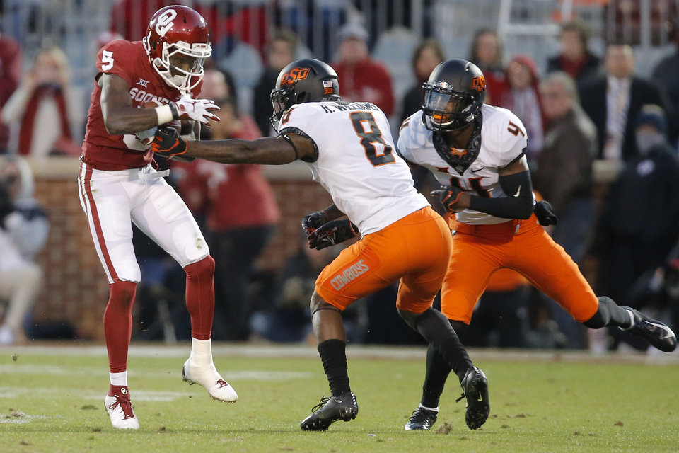 Photo - Oklahoma's Marquise Brown (5) gets between Oklahoma State's Rodarius Williams (8) and A.J. Green (4) during a Bedlam college football game between the University of Oklahoma Sooners (OU) and the Oklahoma State University Cowboys (OSU) at Gaylord Family-Oklahoma Memorial Stadium in Norman, Okla., Nov. 10, 2018.  Photo by Bryan Terry, The Oklahoman