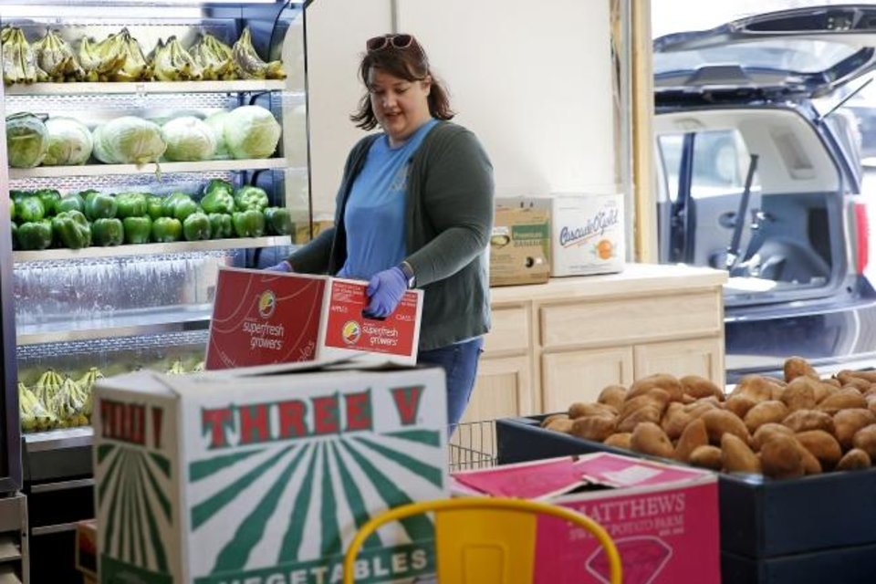 Photo -  Sara Hawk with Restore OKC carries produce inside The Market at Restore OKC in the North Creston Hills neighborhood. [Bryan Terry/The Oklahoman]