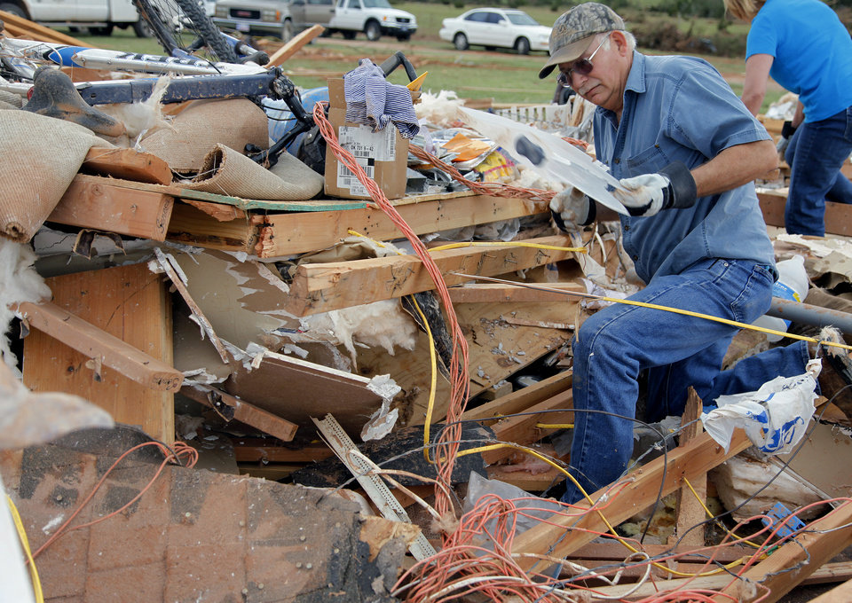 Photo - Tom Green helps recover items out of his daughter's home that was destroyed by Tuesday's tornado west of El Reno, Wednesday, May 25, 2011. Photo by Chris Landsberger, The Oklahoman