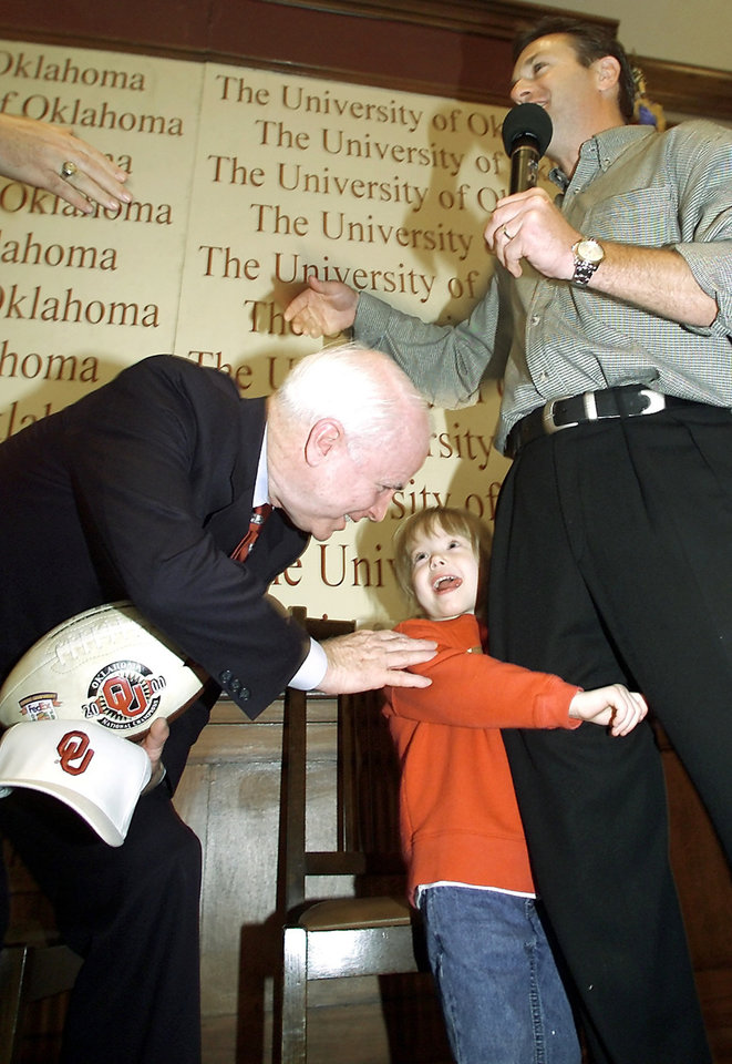 Photo - U.S. Senator John McCain, R-Ariz., bends down to meet Mackenzie Stoops after her father, OU football coach Bob Stoops presented McCain with a signed football and hat during his speech about campaign finance reform in the ballroom of the student union at the  University of Oklahoma