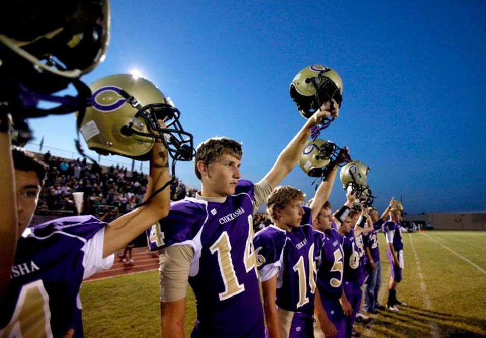 Photo -  Chickasha players raise their helmets during the opening kickoff of the football game between Chickasha and Capitol Hill at Chickasha High School, Friday, Oct. 1, 2010.  It was the first home game since the death of player Kody Turner.