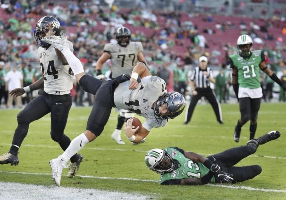 Photo -  Central Florida quarterback Dillon Gabriel (11) leaps into the end zone for a touchdown over Marshall safety Nazeeh Johnson (13) during the Gasparilla Bowl on Monday in Tampa, Fla. [Stephen M. Dowell/Orlando Sentinel via AP]