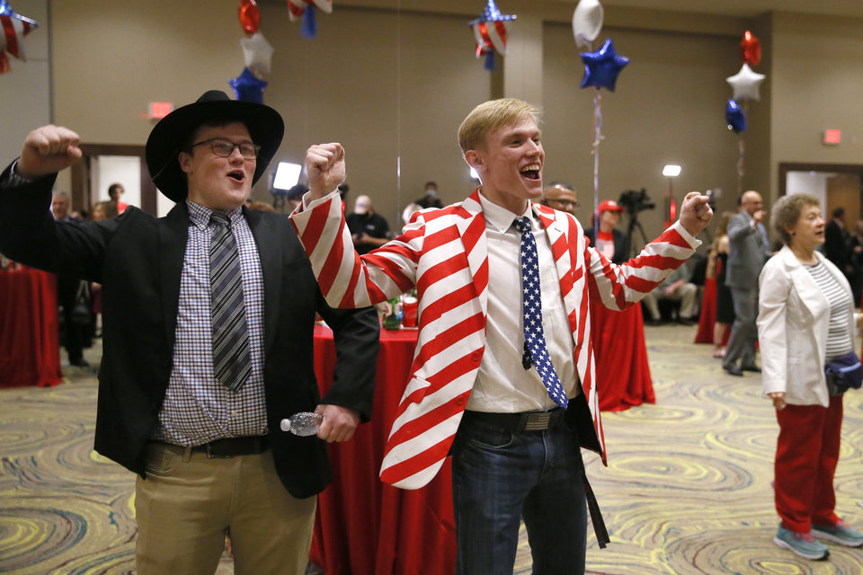 Photo - Gideon Bodley, left, and Caleb McQuay celebrate as they watch election results during a Republican Party election night watch party in Edmond, Tuesday, Nov. 3, 2020. [Bryan Terry/The Oklahoman]