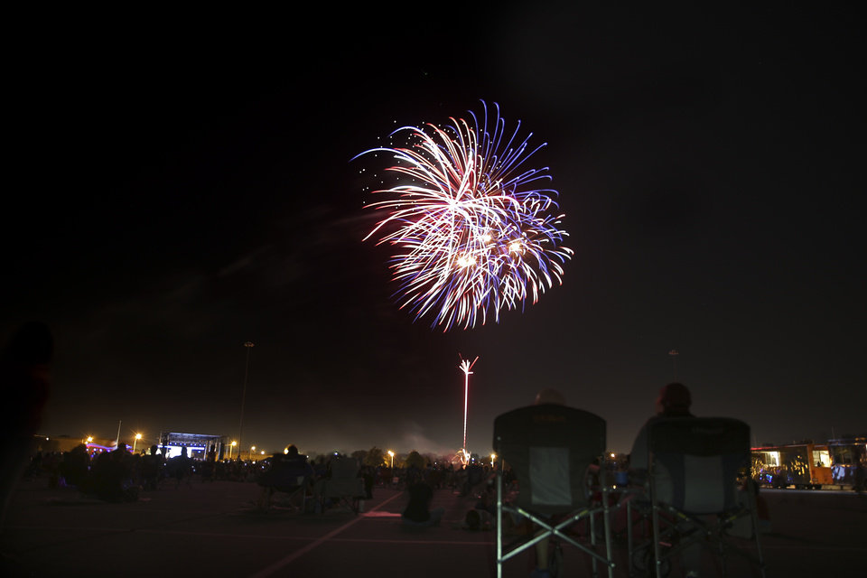 Photo - People watch fireworks during the Oklahoma City Philharmonic's Red, White and Boom fireworks and concert at the State Fair Park in Oklahoma City,  Tuesday, July 3, 2018. Photo by Sarah Phipps, The Oklahoman