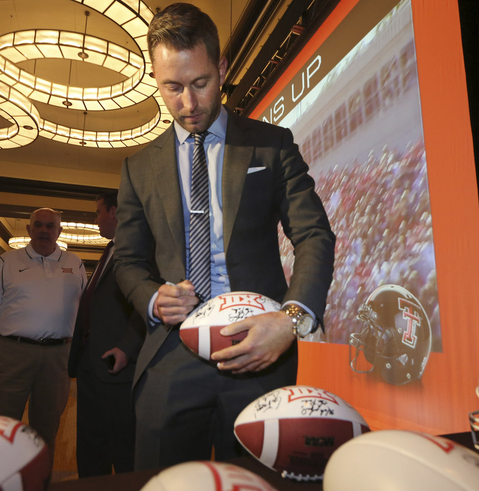 Photo - Texas Tech football coach Kliff Kingsbury signs a football during the NCAA college Big 12 Conference football media days in Dallas, Monday, July 21, 2014. (AP Photo/LM Otero)