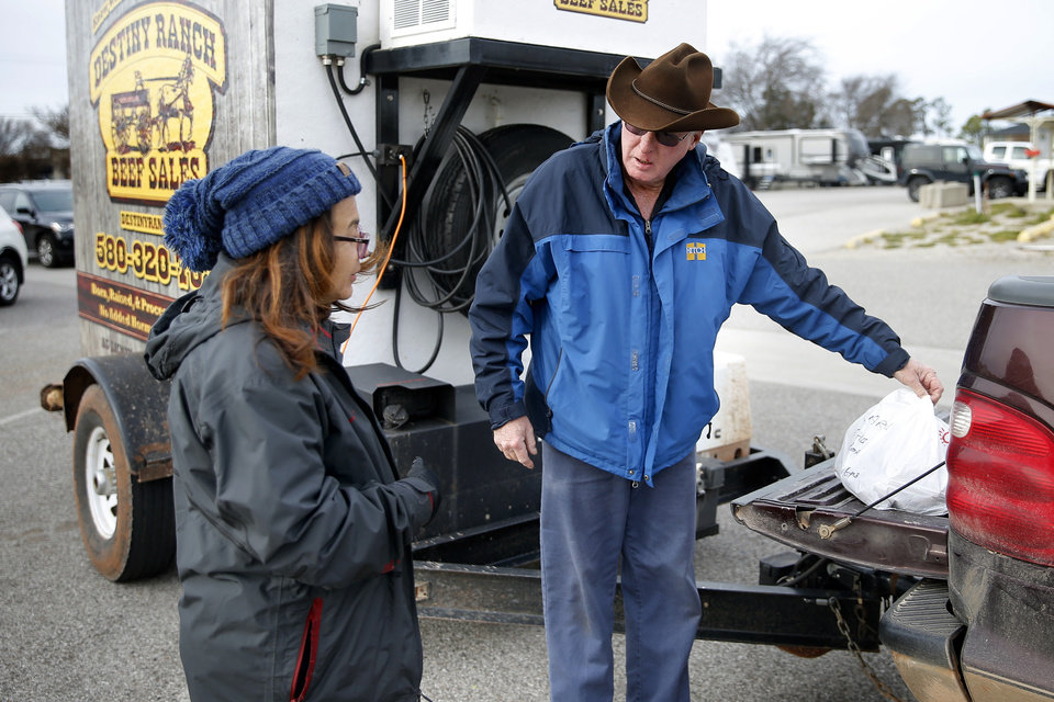 Photo - Willaim Payne with Destiny Ranch gives Carmen VanHootegem her beef order at the Cleveland County Fairgrounds in Norman, Okla., Saturday, March 21, 2020. The weekly Norman Farm Market was closed to walk up business but customers were able to pick up orders placed in advance. [Bryan Terry/The Oklahoman]