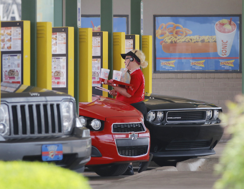 Photo - Sonic car hops hustle around the drive-in at 900 W. Sheridan during lunch Wednesday, May 23, 2018. Photo by Doug Hoke,The Oklahoman