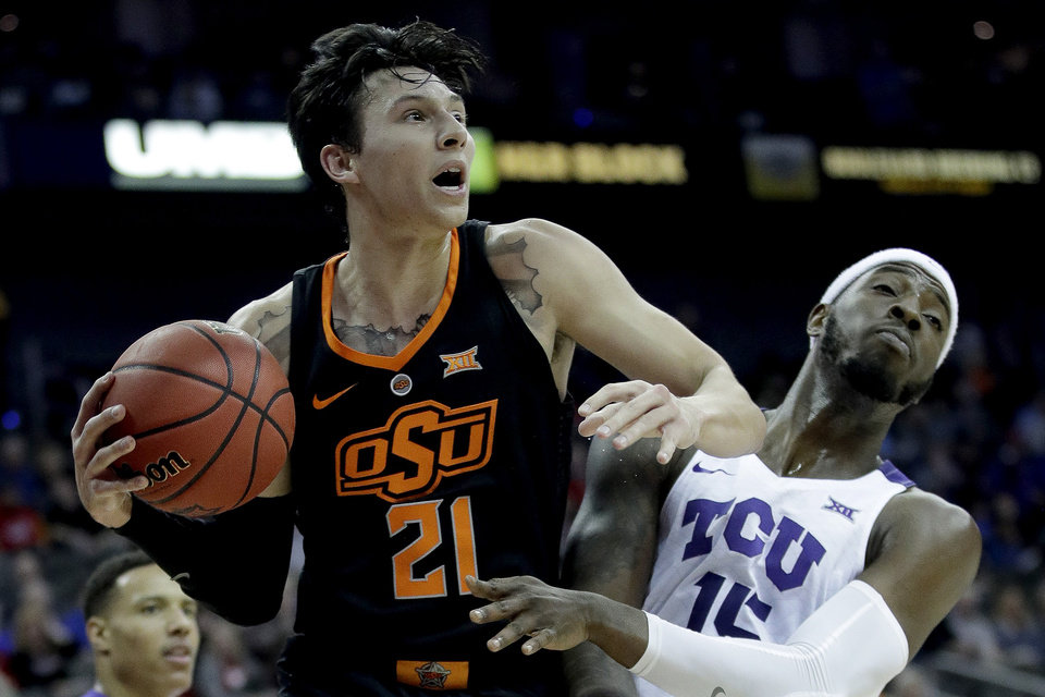 Photo - Oklahoma State's Lindy Waters III, left, beats TCU's JD Miller to a rebound during the first half of an NCAA college basketball game in the Big 12 men's tournament Wednesday, March 13, 2019, in Kansas City, Mo. (AP Photo/Charlie Riedel)