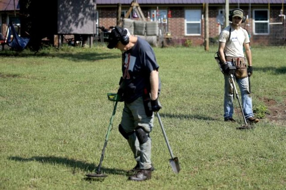 Photo - Matthew Fortney, at right, of Pawhuska, Okla, listens for tones while metal detecting in Fallis, Okla., Saturday, Sept. 14, 2019. [Bryan Terry/The Oklahoman]